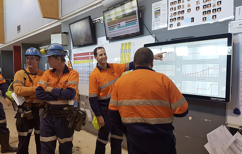 men standing reviewing information on a digital display in a mining environment